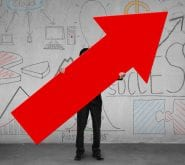 Man Holding Red Arrow Pointing Upward with Graphs and Charts Behind Him on Wall