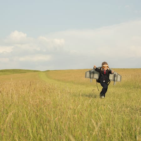 little boy dressed in suit with rocket running in a field