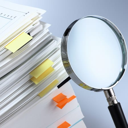 Investigate and analyze. Scanning business documents. Magnifying glass and stack of documents.