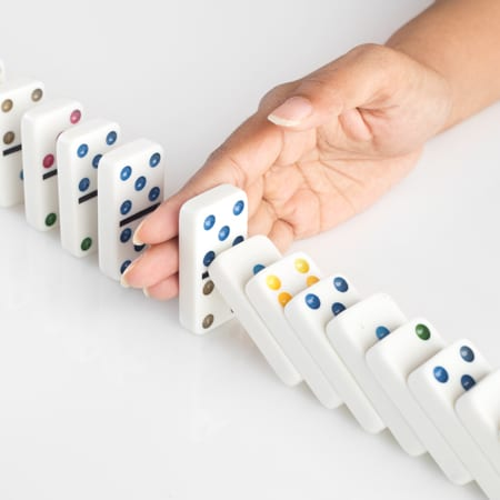 Dominoes Falling Stopped by Hand