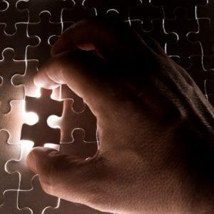 hand placing puzzle piece
